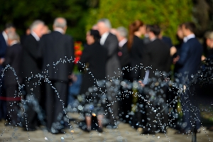 Blurred people in black suits on funeral
